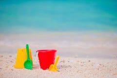 Juguetes de la playa del niño en la arena blanca Cubos y cuchillas para los niños en la playa arenosa blanca después de los juego Imágenes de archivo libres de regalías