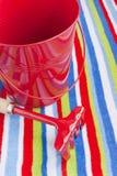 Juguetes de los niños rojos de la toalla de playa del verano Imagen de archivo libre de regalías