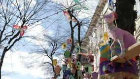 Juguetes de lujo y linternas coloridos, adornados como pajareras, balanceando en árbol deshojado en la calle europea de la ciudad almacen de video