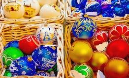 Juguetes del árbol de navidad apilados en una caja de mimbre Fotografía de archivo libre de regalías