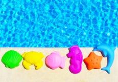 Juguetes del bebé en el fondo de la piscina Fotografía de archivo
