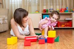 Juguetes del juego de la mamá y del niño en casa Fotos de archivo libres de regalías