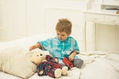 Juguetes del juego de niños Juego del niño pequeño en casa Niño pequeño que juega con el oso día feliz de la familia y de los niñ fotografía de archivo