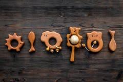 Juguetes hechos a mano de madera lindos para recién nacido en copyspace de madera oscuro de la opinión superior del fondo Imagen de archivo libre de regalías