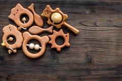 Juguetes hechos a mano de madera lindos para recién nacido en copyspace de madera oscuro de la opinión superior del fondo Fotos de archivo libres de regalías