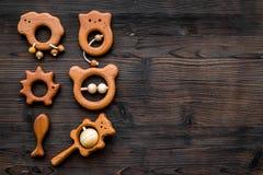 Juguetes hechos a mano de madera lindos para recién nacido en copyspace de madera oscuro de la opinión superior del fondo Fotografía de archivo libre de regalías