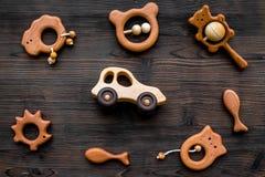 Juguetes hechos a mano de madera lindos para recién nacido en la opinión superior del fondo de madera oscuro Fotografía de archivo libre de regalías