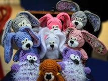 Juguetes hechos punto en un pecho - conejos y osos handmade Imagen de archivo libre de regalías