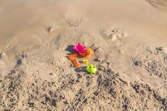 Juguetes olvidados en una playa arenosa Imágenes de archivo libres de regalías