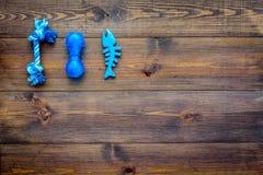 Juguetes para el perro y el gato de animales domésticos Accesorios de goma en espacio de madera oscuro de la copia de la opinión  Fotografía de archivo libre de regalías