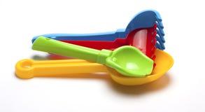 Juguetes plásticos coloreados para la salvadera en un fondo blanco Fotografía de archivo