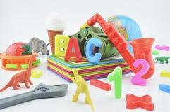Juguetes plásticos en el fondo blanco, concepto de la educación de los niños Foto de archivo libre de regalías