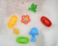 Juguetes que flotan en el baño con espuma Foto de archivo libre de regalías