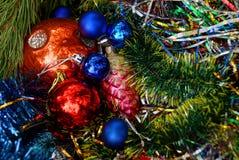 Juguetes y bolas coloreados hermosos del ` s del Año Nuevo en ramas coníferas verdes Foto de archivo libre de regalías