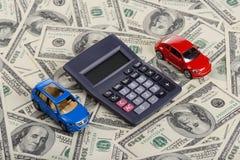 Juguetes y calculadora del coche entre los dólares Fotografía de archivo libre de regalías