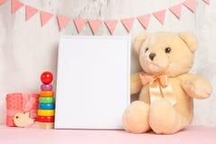 Juguetes y marco del bebé en fondo ligero de la pared, para el diseño Ducha de bebé imagenes de archivo