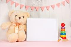 Juguetes y marco del bebé en fondo ligero de la pared, para el diseño Ducha de bebé fotografía de archivo libre de regalías