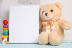 Juguetes y marco del bebé en fondo ligero de la pared, para el diseño Ducha de bebé foto de archivo libre de regalías