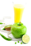 Juice,apple,lime,peas,kiwi and measure tape Royalty Free Stock Photography