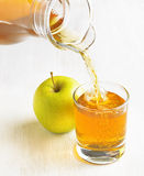 Apple juice pouring from jug into a glass Royalty Free Stock Photo