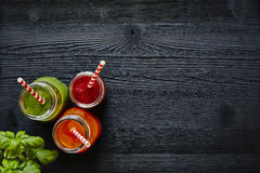 Juice bar three colorful juices with straws on dark wooden surface stock photos
