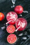 Juice of blood orange, fruit halves and ice, top view, stock photos