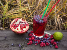 Juice bubble tea with pomegranate, green tea and raspberry on a wooden background Royalty Free Stock Photo