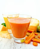 Juice carrot and pumpkin with vegetables on light board Royalty Free Stock Photo