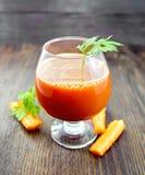 Juice carrot in wineglass on board Royalty Free Stock Photo