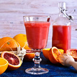 The juice from citrus fruits. The juice of red and orange oranges in a glass beaker surrounded by whole and cut fruits in rustic style Stock Image