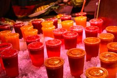 Juice. Close up of many cups of colourful red orange yellow green fresh lean healthy fruit juice on ice in La Boqueria market in Barcelona, Spain royalty free stock images