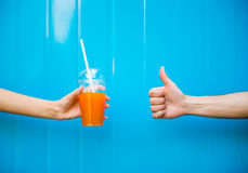 Juice. Close-up of woman's hand is holding juice against the blue wall and another hand is showing thumb up Royalty Free Stock Image