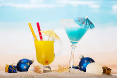 Juice, cocktail, starfish, christmas balls, gifts in sand against sea. Stock Photo
