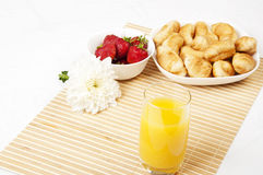 Juice, croissants and Berries On a bamboo napkin. Light Breakfast: orange juice, croissants and Berries on a table Stock Image