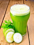 Juice cucumber in tall glassful on board Stock Image