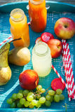 Juice Different Colors Bottles Fruits on Blue Tray Royalty Free Stock Photography