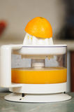 Juice extractor. Squeezing of orange juice on a juice extractor Royalty Free Stock Photography
