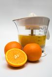 Juice extractor with juice. Modern juice extractor with juice and ripe oranges Royalty Free Stock Image