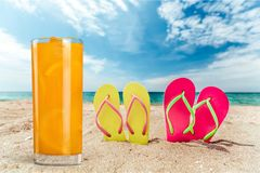 Juice and flip flops on beach. Ice water tea glass cold lemon Royalty Free Stock Photography