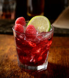 The juice of fresh raspberries in a glass with ice and a lemon on a brown background. Juice of fresh raspberries served with ice in a glass Stock Image