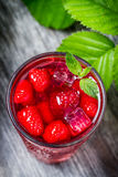 Juice with fresh raspberries and ice. Closeup of juice with fresh raspberries and ice on old wooden table Stock Photos