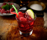 The juice of fresh raspberries with ice in a glass, a plate of fruit and sugar in the background. Juice of fresh raspberries served with ice in a glass Stock Images