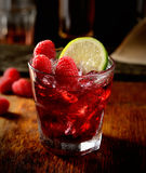 The juice of fresh raspberries with ice in a glass, a plate of fruit and sugar in the background Royalty Free Stock Photos