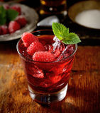 The juice of fresh raspberries with ice in a transparent glass on a wooden background. Juice of fresh raspberries served with ice in a glass Stock Photos