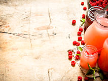 The juice of fresh raspberries and jam. On a wooden table Royalty Free Stock Photos