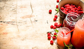 The juice of fresh raspberries and jam. On a wooden table Stock Image