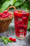 Juice of fresh raspberries served with ice in a glass. On old wooden table Royalty Free Stock Photo