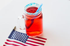 Juice glass and american flag on independence day Stock Photos