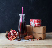 Juice in glass bottle and pomegranate with gift Stock Image