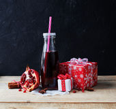 Juice in glass bottle and pomegranate with gift Stock Photography